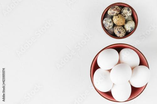 Fototapeta Egg concept for Easter - quail eggs and chicken eggs in bowls on a white table obraz