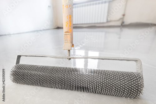 Fototapeta Close-up leveling tool for self-leveling floor. Leveling with a mixture of cement floors with a needle roller obraz