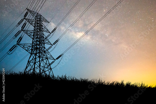Fototapeta The silhouette of the high voltage transmission tower has a complex steel structure. High voltage pole silhouette In the meadow there is a background of the night sky and the milky way. obraz