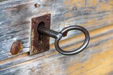 Old Rusty Key In Wooden Doors.