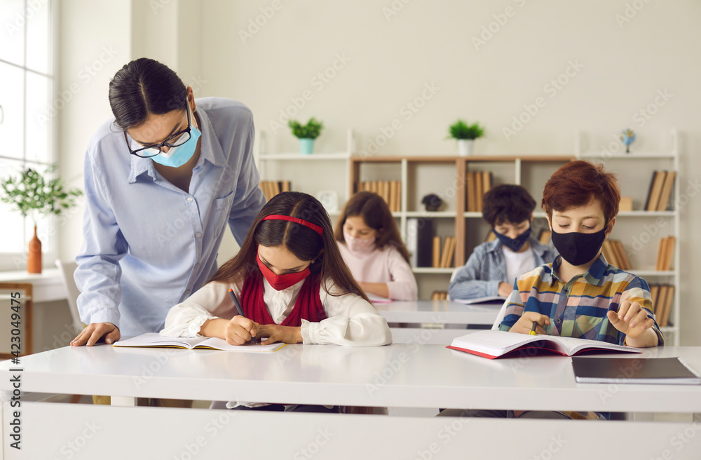 Fototapeta Back at school with safety measures against coronavirus respiratory infection. Students and teacher wearing face masks in class. Children with mouths and noses covered sitting at desks in classroom