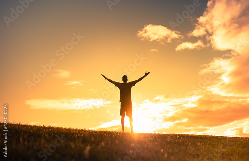 Fototapeta Young man in nature facing the sunrise lifting his arms up to the sky. Positivity, and feeling inspired concept.  obraz
