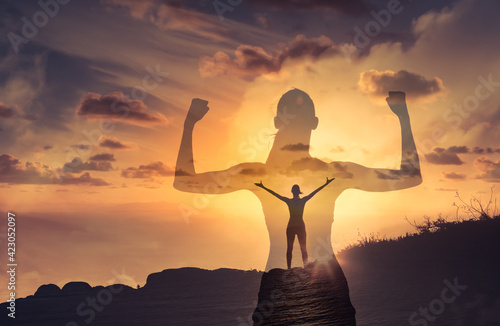 Strong confident woman flexing arms facing the sunset. People feeling inspire, and having inner strength concept.