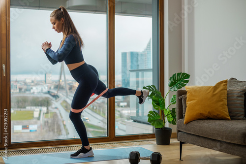 Fototapeta Brunette in tracksuit practices exercises with stretch strap obraz