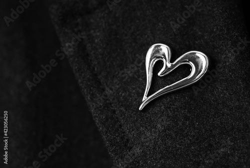 Fotografija wool coat lapel with elegant metal brooch in the shape of a heart, black and whi