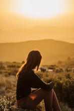 Side View Of Peaceful Female Traveler Sitting On Hill With Closed Eyes And Enjoying Nature In Highlands At Sundown