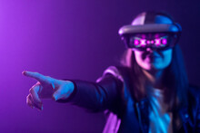 Unrecognizable Female With Outstretched Arm Wearing VR Headset While Exploring Virtual Reality Under Blue Neon Light