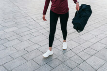 Crop Fit Female In Trendy Sportive Outfit And Sneakers Carrying Handbag While Walking On Paved City Square