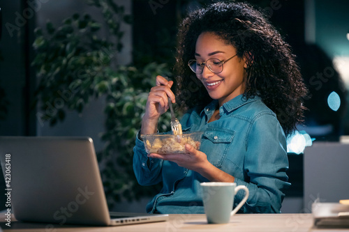 Fotografija Beautiful afro young business woman working with computer while eating pasta sitting in the office