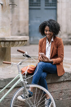 Young African American Female In Stylish Casual Outfit Browsing Mobile Phone While Sitting Near Bicycle On Old Stone Fountain Border In City