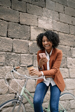 Delighted African American Female Standing Near Parked Bike With Takeaway Drink And Messaging On Social Media On Smartphone On Street