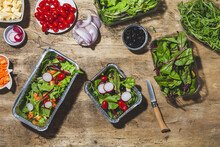 Top View Composition Of Delicious Vegetable Salads In Foil Bowls Placed On Table Near Various Ingredients Including Cherry Tomatoes Onions Radish And Carrots