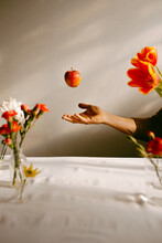 Crop Anonymous Person Tossing Ripe Apple In Air Above Table With Tulips And Fresh Carnations