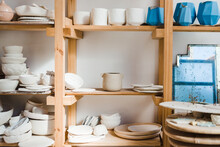 Collection Of Handmade Ceramic Bowls And Vases With Pots And Plates With Old Mirror Near Different Types Of Utensil Standing On Wooden Shelves In Light Studio