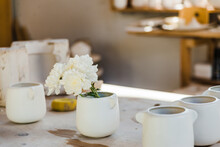 Set Of White Ceramic Cups With Flowers Placed On Counter In Light Studio Near Objects For Handicraft