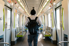 Back View Of Anonymous Male Student With Backpack Riding Modern Train While Commuting To University