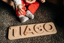 Cropped Unrecognizable Little Baby Playing On Floor With Wooden Toy With Tiago Name Letters