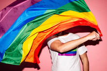 Unrecognizable Homosexual Male In White T Shirt Waving LGBT Flag Against Pink Background