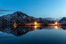Scenic View Of Wooden Piers In Harbor With Illuminated Lamps Located Near Sea In Mountainous Terrain In Evening In Norway