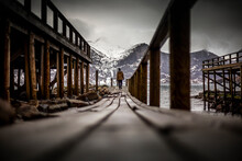 Ground Level Back View Of Explorer Walking Along Wooden Quay Near Sea In Mountainous Terrain In Winter In Norway
