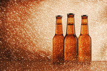 Glass Bottle Of Cold Beer Surrounded By Sparkling Lights On Bright Background