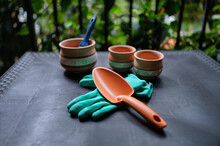 From Above Of Collection Of Gardening Tools And Ceramic Pots For Transplanting Plants Placed On Table In Greenhouse