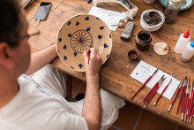 From Above Of Crop Faceless Man Sitting At Table With Brushes And Drawing Sketches On Handmade Ceramic Plate