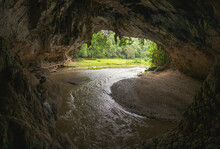 Picturesque Scenery Of Narrow River Flowing Through Tham Lot Cave Covered With Lush Green Tropical Vegetation In Thailand