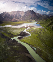 Amazing View Of Curvy Blue River Loop Streaming On Rough Hilly Terrain Covered With Lush Abundant Vegetation In Iceland