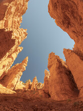 From Below Of Tall Rocky Cliffs With Uneven Surface Located In Arid Terrain Against Cloudless Sky In Sunny Bryce Canyon In USA
