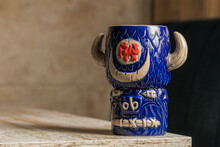 Bull Shaped Tiki Mug Of Alcohol Drink With Froth Placed Against Wooden Table On Blurred Background