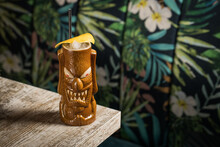 Brown Sculptural Tiki Mug With Alcohol Drink Decorated With Straw And Ice Placed On Table On Blurred Background