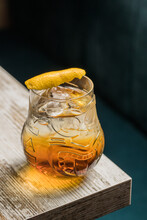 From Above Of Tiki Glass Mug With Booze Placed On Edge Of Wooden Table In Room On Blurred Background