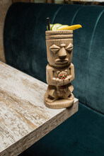 Traditional Sculptural Tiki Cup Of Alcohol Drink With Straw Placed On Wooden Table