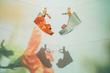 Trendy Sandals Hanging On Rope Against Wall With Projection Of Flower In Summer