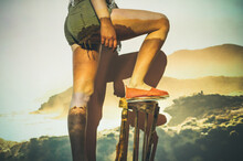 Anonymous Woman In Shorts Climbing Chair Against Wall With Mountains And Sea Projection
