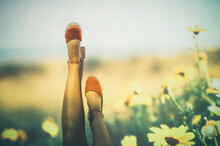 Anonymous Female In Summer Shoes Swinging Legs Against Projection Of Field With Yellow Flowers