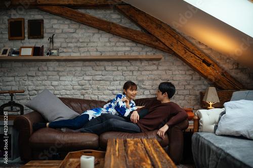 Lovely japanese couple chilling on sofa at home Fotobehang