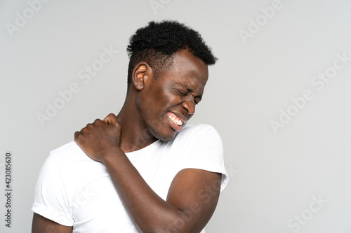 Unhappy Black man suffering from neck pain, pinched nerve in her back. African male has spinal problem, shoulder stiffness, muscle inflammation, rheumatoid pain isolated on studio grey background.