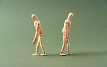 Two Wooden Figures Walking Away From Each Other On Green Background