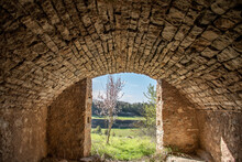Old Stone Building With Arched Roof Opening To The Outside Where You Can See A Flowering Almond Tree And Fields.