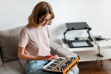 Woman Hands Playing Minilogue Synthesizer Using Mobile App At Home
