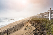 Foggy Morning On A Sandy Beach Lined With Grassy Sand Dunes And Holiday Homes In Autumn. Lens Flare.