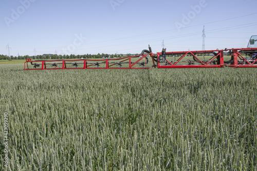 Fototapeta Opryskiwacz na polu pszenicy obraz
