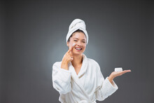 Beauty Hydrating Moisturizer And Skincare Routine. Woman In A Bathrobe And A Towel Holds The Cream And Applying Moisturizing Cream On The Cheek While Standing In Front Of A Grey Background