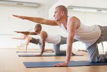 Positive Man Practicing Balancing Table Pose (Dandayamna Bharmanasana) To Improve Balance, Coordination And Core Strength During Group Yoga Training..