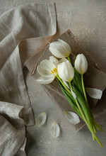 White Tulip On An Old Book And A Napkin On The Side