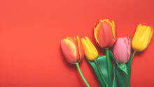 Floral Background With Bouquet Made Of Yellow And Pink Tulips On Orange Background. Flat Lay, Top View. Woman Day Background.