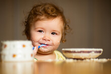 Cute Little Baby Is Being Fed Using Spoon. Little Child Eating Fruit Puree Indoors.