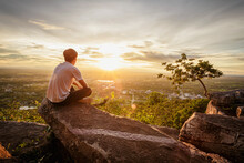 Man Sitting Relax On Top Of A Moutain Watching The Sunset